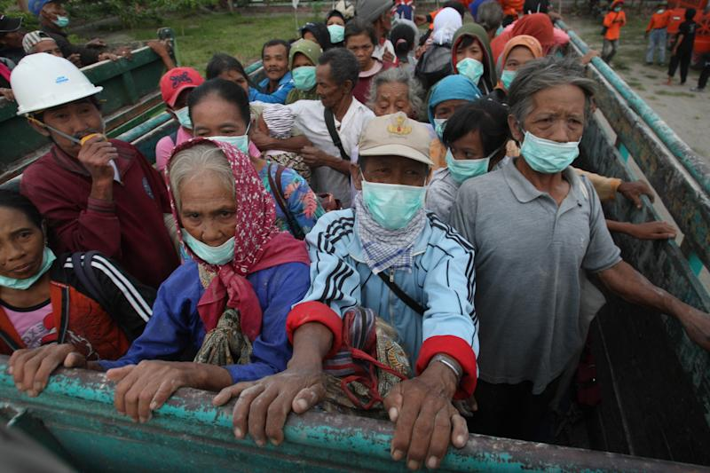 Villagers evacuate from their homes on the slope of Mount Kelud which erupted in Blitar, Indonesia, Friday, Feb 14, 2014. An explosive volcanic eruption on Indonesia's most populous island blasted ash and debris 18 kilometers (12 miles) into the air Friday, killing two people while forcing authorities to evacuate more than 100,000 and close six airports. (AP Photo/Trisnadi)