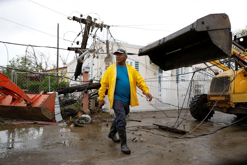 Workers use backhoe loaders to remove damaged electrical installations from a street in Salinas, Puerto Rico, Sept. 21, 2017. (Carlos Garcia Rawlins / Reuters)