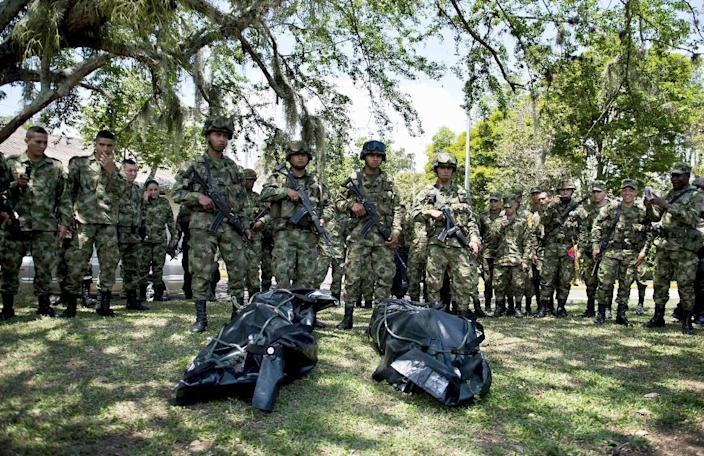 Colombian soldiers stand in Buga, Colombia, next to the corpses of Revolutionary Armed Forces of Colombia (FARC) leftist guerrilla fighters on September 26, 2014 (AFP Photo/Luis Robayo)