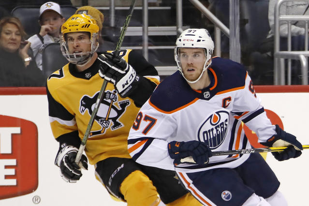 FILE - In this Nov. 2, 2019, file photo, Edmonton Oilers' Connor McDavid (97) and Pittsburgh Penguins' Sidney Crosby (87) skate during the second period of an NHL hockey game in Pittsburgh. Edmonton Oilers captain Connor McDavid is still regarded as the NHLs top forward, while peers consider Pittsburghs Sidney Crosby the game's most complete player, according to the NHL Players Associations annual poll of players released Tuesday, March 31, 2020. (AP Photo/Gene J. Puskar, File)