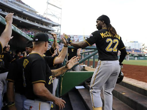 Pittsburgh Pirates' Andrew McCutchen (22) celebrates his two-rum home with teammates in the dugout against the Washington Nationals during the first inning of a baseball game, Monday, July 22, 2013, in Washington. (AP Photo/Nick Wass)