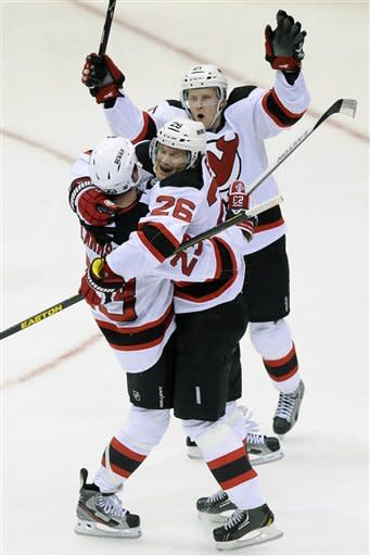 New Jersey Devils' David Clarkson (23), Patrik Elias (26) and Mattias Tedenby (21) celebrate Clarkson's goal against the New York Islanders in the third period of an NHL hockey game on Saturday Jan., 19, 2013 at Nassau Coliseum in Uniondale, N.Y. The Devils won 2-1. (AP Photo/Kathy Kmonicek)