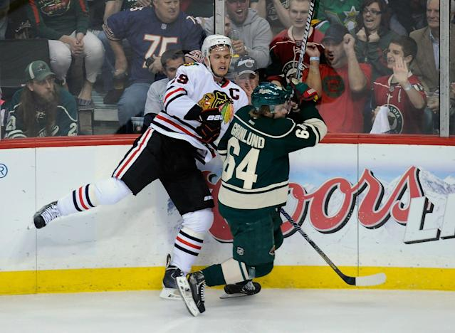 ST PAUL, MN - MAY 13: Mikael Granlund #64 of the Minnesota Wild checks Jonathan Toews #19 of the Chicago Blackhawks into the boards during the first period in Game Six of the Second Round of the 2014 NHL Stanley Cup Playoffs on May 13, 2014 at Xcel Energy Center in St Paul, Minnesota. (Photo by Hannah Foslien/Getty Images)