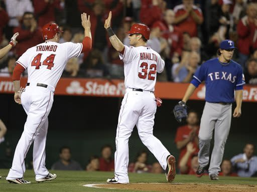 Los Angeles Angels' Mark Trumbo, left, and Josh Hamilton high-five after they scored on a double by Howie Kendrick during the fourth inning of a baseball game against the Texas Rangers in Anaheim, Calif., Monday, April 22, 2013. Texas Rangers starting pitcher Derek Holland, background right, watches. (AP Photo/Jae C. Hong)