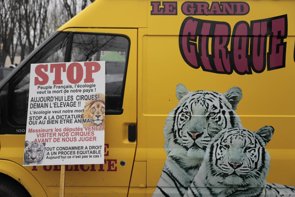 """A poster is seen at a circus workers van during a protest near the National Assembly, Tuesday, Jan.26, 2021. French lawmakers start debating Tuesday a bill that would ban using wild animals in traveling circuses and keeping dolphins and whales in captivity in marine parks, amid other measures to better protect animal welfare. Circus workers stage a protest outside the National Assembly to denounce what they consider """"a mistake."""" (AP Photo/Lewis Joly)"""