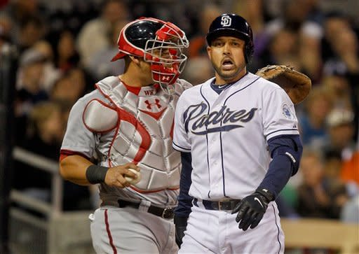 San Diego Padres' Jason Bartlett, right, walks away from home plate as Washington Nationals catcher Wilson Ramos prepares to throw back to the pitcher after Bartlett struck out with the bases loaded during the fourth inning of a baseball game on Thursday, April 26, 2012, in San Diego. (AP Photo/Lenny Ignelzi)