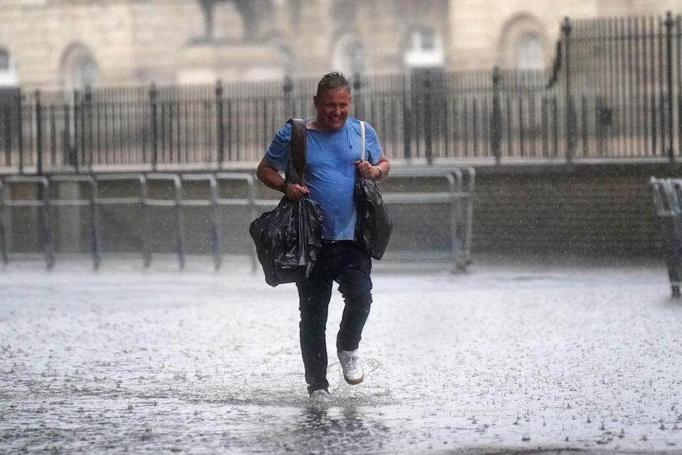 A man walks through flood water in in central London. Thunderstorms are being forecast (PA) (PA Wire)