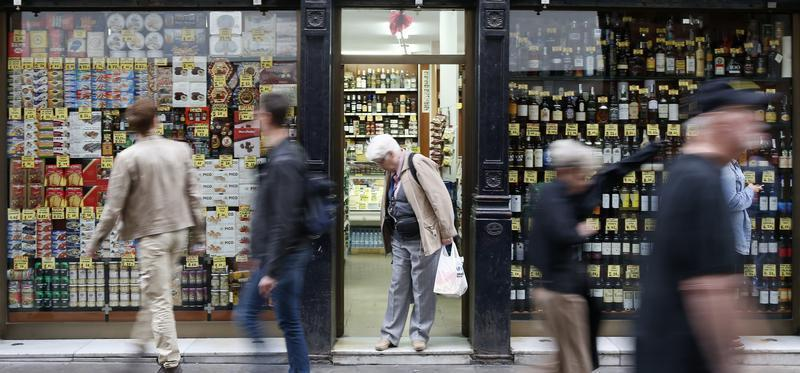 A woman leaves a food shop as people walk past it in central Barcelona