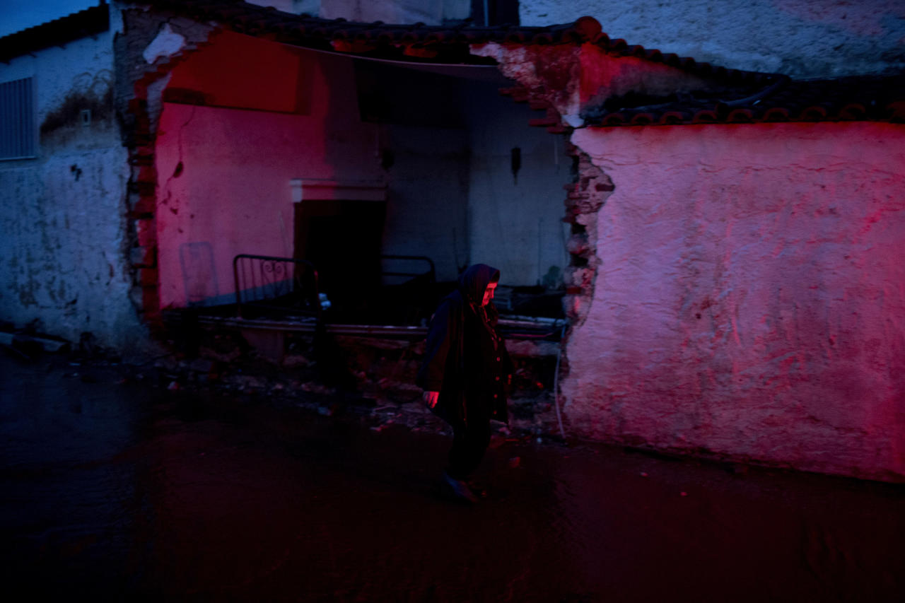 <p>A elderly woman walks in front of a damaged house in the town of Mandra western Athens, on Friday , Nov. 17, 2017. (Photo: Petros Giannakouris/AP) </p>