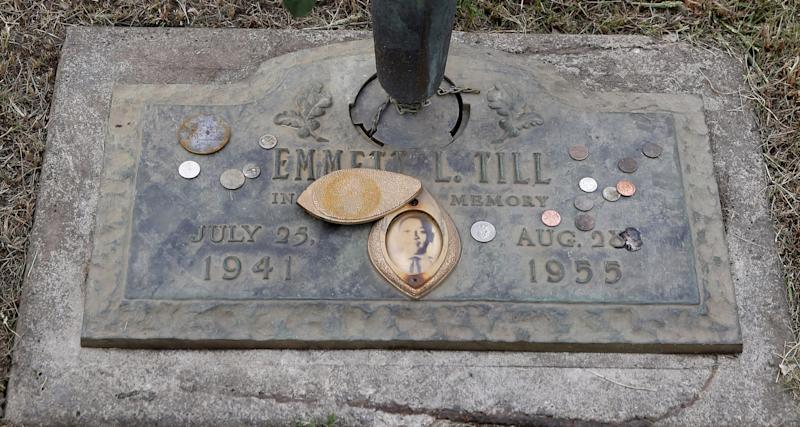 The grave marker of Emmett Till has a photo of Till and coins placed on it during a gravesite ceremony at the Burr Oak Cemetery marking the 60th anniversary of the murder of Till in Mississippi, Friday, Aug. 28, 2015, in Alsip, Ill. (AP Photo/Charles Rex Arbogast)
