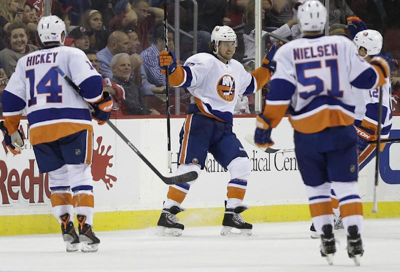 New York Islanders right wing Michael Grabner, center, of Austria, celebrates with teammates after scoring a goal against the New Jersey Devils during the second period of an NHL hockey game, Friday, Oct. 4, 2013, in Newark, N.J. (AP Photo/Julio Cortez)