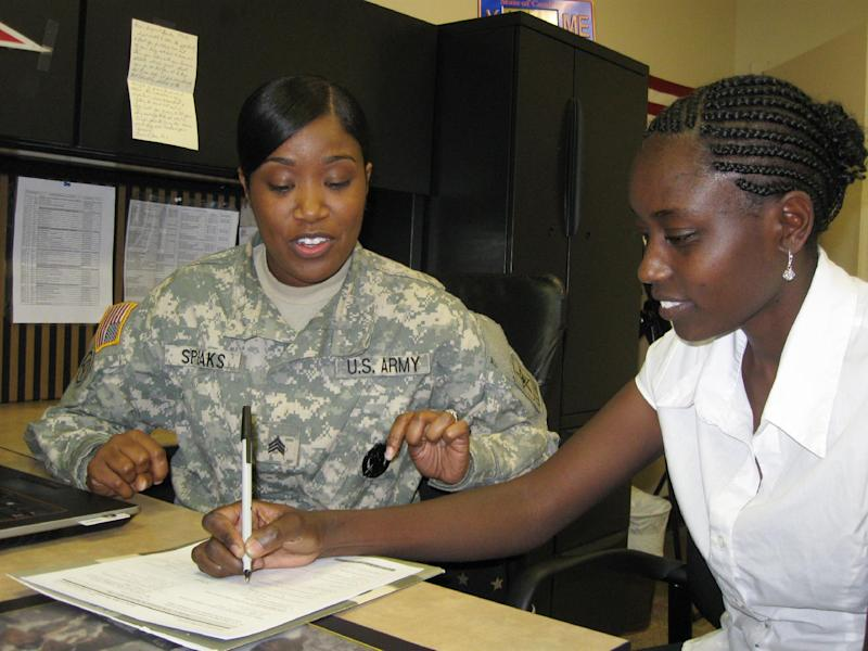 In this Jan. 24, 2013 photo, Army Sgt. Keawanyda Speaks,  left, helps recruit Carolyne Chelulei,  fill out documents while visiting the Army recruiting office in Spartanburg, S.C. Chelulei is a native of Kenya, plans to join the Army to train as a psychiatrists' assistant. Serving in the Army in a medical specialty allows the 23-year-old to get on a fast track to U.S. citizenship. ( AP Photo/Susanne M. Schafer)