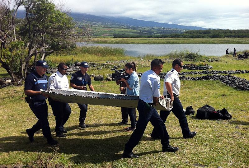 Police on Reunion island carry a wing part from flight MH370, on July 29, 2015 (AFP Photo/Yannick Pitou)