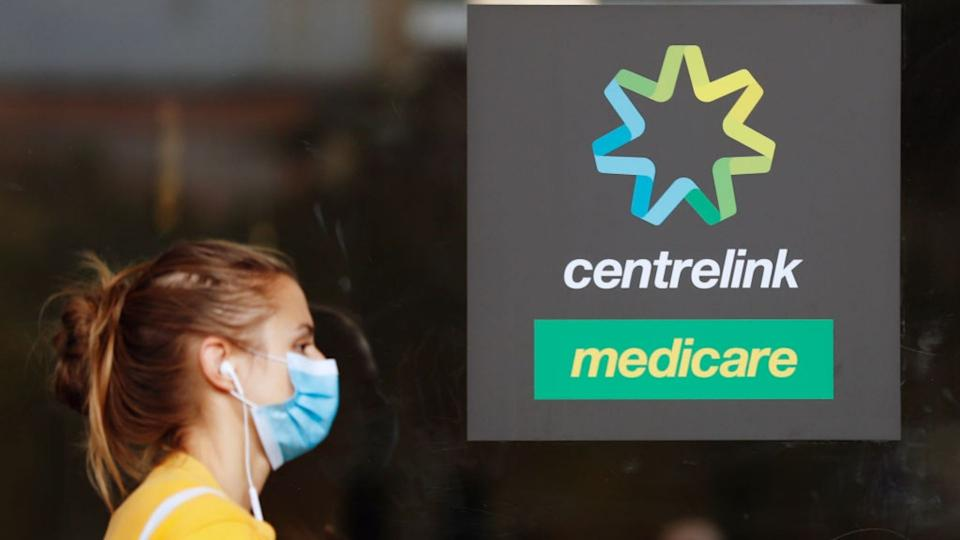 Young woman wearing face mask walks past Centrelink, Medicare sign.