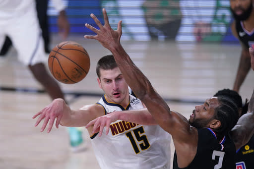 Denver Nuggets center Nikola Jokic (15) passes to ball past Los Angeles Clippers forward Kawhi Leonard (2) during the first half of an NBA conference semifinal playoff basketball game Tuesday, Sept. 15, 2020, in Lake Buena Vista, Fla. (AP Photo/Mark J. Terrill)