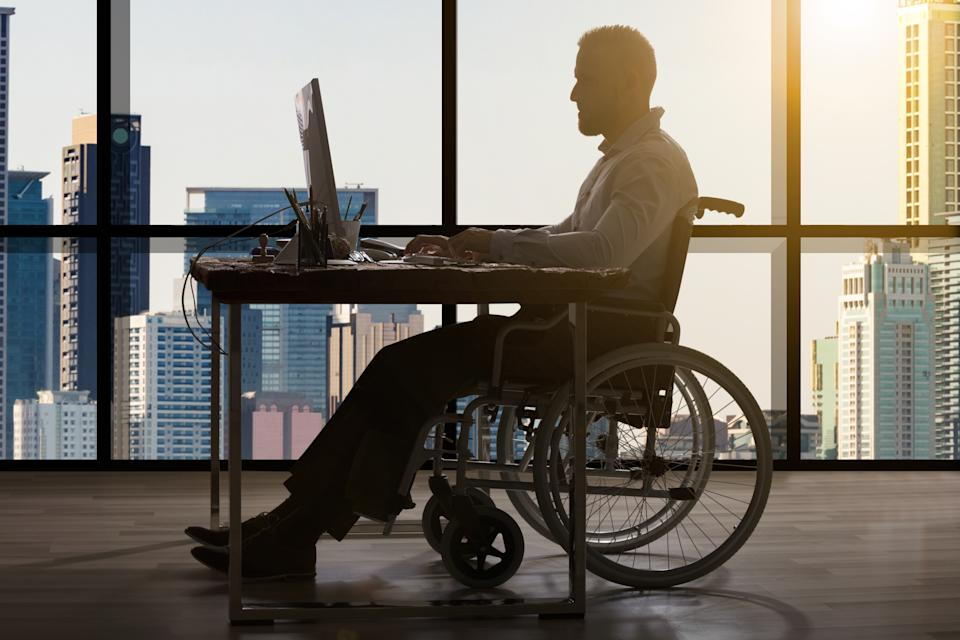 Disabled Businessman Sitting In Wheelchair Using Computer At Workplace