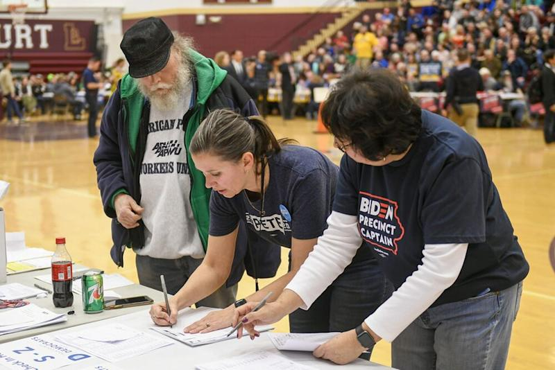 Precinct officials tally the votes during a caucus at Lincoln High School in Des Moines, Iowa, on Monday.   CRAIG LASSIG/EPA-EFE/Shutterstock