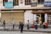 """People in masks maintain social distancing as they queue to buy groceries in Thimphu, Bhutan. The Himalayan kingdom says it will only start vaccinating citizens on an """"auspicious"""" date"""
