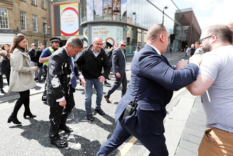 Brexit Party leader Nigel Farage gestures after being hit with a milkshake while arriving for a Brexit Party campaign event in Newcastle, Britain, May 20, 2019. REUTERS/Scott Heppell