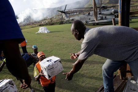 Haitians load supplies delivered by a Marines helicopter after Hurricane Matthew in Les Anglais, Haiti, October 11, 2016. REUTERS/Andres Martinez Casares