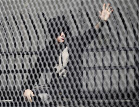 Pop singer Justin Bieber waves to fans as he leaves a jail after being released on bail in Miami, Florida January 23, 2014. REUTERS/Andrew Innerarity