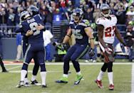 Seattle Seahawks holder Jon Ryan (9) hugs kicker Steven Hauschka, left, after Hauschka kicked the game-winning field goal in overtime against the Tampa Bay Buccaneers in an NFL football game Sunday, Nov. 3, 2013, in Seattle. The Seahawks won 27-24 in overtime. At right, the Seahawks' Zach Miller (86) and Tampa Bay Buccaneers' Johnthan Banks (27) watch. (AP Photo/Elaine Thompson)