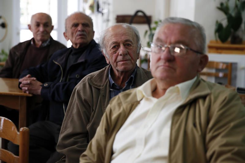 In this Tuesday, May 14, 2019, photo, pensioners sit at a community center for the retired in Karpenisi town at Evrytania region, in central Greece. The area, a winding, three-hour drive from Athens, has the oldest population in the whole European Union, 54.3 on average. (AP Photo/Thanassis Stavrakis)