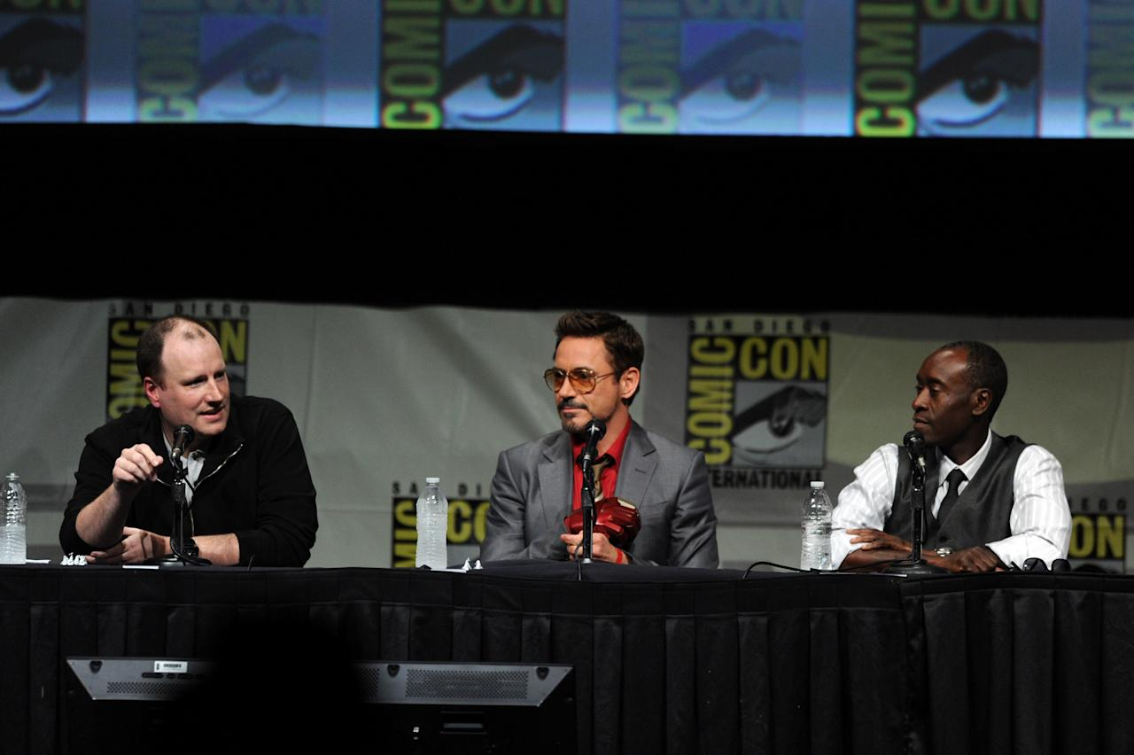 """SAN DIEGO, CA - JULY 14:  (L-R) Producer Kevin Feige, actors Robert Downey Jr., and Don Cheadle speak at Marvel Studios """"Iron Man 3"""" panel during Comic-Con International 2012 at San Diego Convention Center on July 14, 2012 in San Diego, California.  (Photo by Kevin Winter/Getty Images)"""