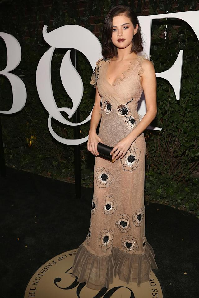 <p>Gomez stripped the coat off for the red carpet, revealing a sheer Rodarte gown with florals and frill detailing. (Photo: Sylvain Gaboury/Patrick McMullan via Getty Images) </p>