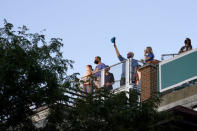 Patrick McCarron, just one of a handful of baseball fans, raises his Chicago Cubs cap from a rooftop venue Friday, Sept. 4, 2020, toward Wrigley Field after the national anthem before a baseball game between the Cubs and St. Louis Cardinals in Chicago. The coronavirus pandemic has been especially hard on businesses that rely on ballpark traffic, eliminating crowds at major league games, and leading to rules that limit the amount of people they can have inside their doors at the same time. (AP Photo/Charles Rex Arbogast)