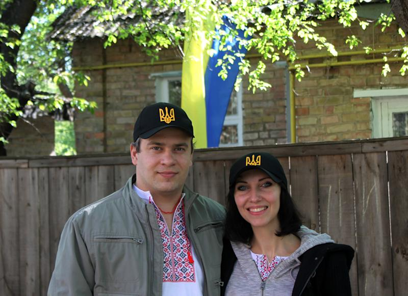 """FILE - In this April. 25, 2014 file photo, Natalia Snihur, 35, and her husband Yehor Korniyev, 35, pose for a photo in front of their home in Kiev, Ukraine, months after they protested with many others to help overthrow what they consider a corrupt, hardline pro-Russian president and bring a new pro-Western government to power. Like many Ukrainians, Snihur and Korniyev are still proud of the popular uprising and hopeful that their country will turn into a dignified European nation, """"Ukraine is being born, it is in labor now, it is giving birth to a nation that will have a conscious national identity,"""" Snihur said during an interview in her family kitchen. (AP Photo/ Maria Danilova, File)"""