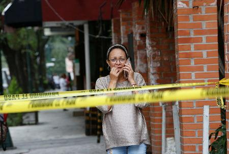 A woman talks on a phone near a building damaged by an earthquake that struck off the southern coast of Mexico late on Thursday in Mexico City