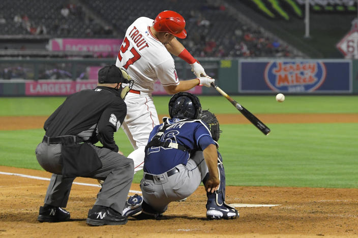 Los Angeles Angels' Mike Trout, center, hits a solo home run as Tampa Bay Rays catcher Francisco Mejia, right, and home plate umpire Sean Barber watch during the sixth inning of a baseball game Tuesday, May 4, 2021, in Anaheim, Calif. (AP Photo/Mark J. Terrill)