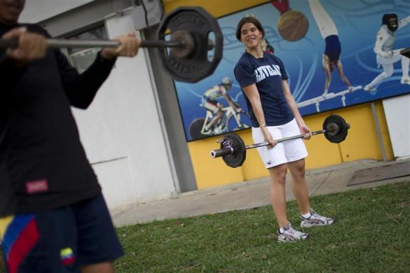 Irene Suarez, 24, a blind runner lifts weights during a training session as part of her Paralympic training route in Caracas March 20, 2012.