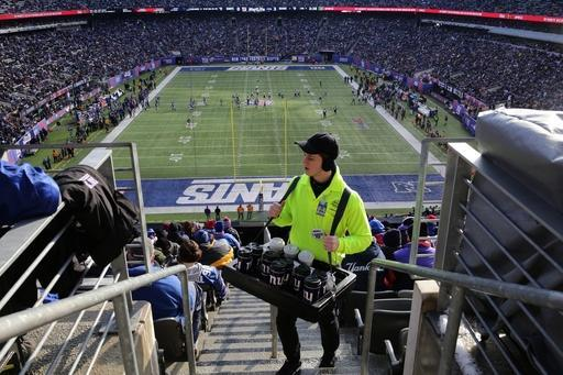 FILE - In this Dec. 15, 2013, file phot, a vendor carries drinks while selling to patrons at MetLife Stadium during the first half of an NFL football game between the Seattle Seahawks and the New York Giants in East Rutherford, N.J. Taylor Turf Installation Inc. is suing the MetLife Stadium's operators and the company that hired the suburban St. Louis company, seeking more than $292,000 that Taylor Turf claims it still is owed for hustling to install the stadium's playing surface last summer. The stadium hosts Super Bowl XLVIII on Sunday, Feb. 2, 2014. (AP Photo/Peter Morgan, File)