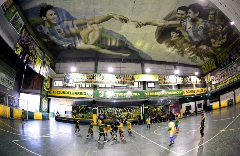 Young people play football at the Sportivo Pereyra club in Barracas, where local artist Santiago Barbeito has painted the sport's version of the Sistine Chapel featuring legends Diego Maradona (R) and Lionel Messi (L)