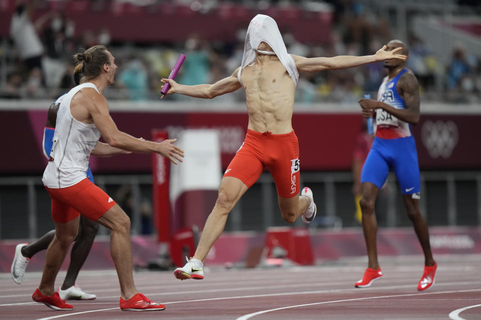 Patrick Grzegorzewicz of Poland celebrates with teammates as he crosses the finish line to win the 4 x 400-meter mixed relay at the 2020 Summer Olympics, Saturday, July 31, 2021, in Tokyo. (AP Photo/David Goldman)