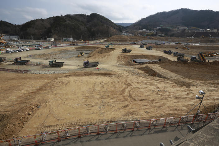 In this March 5, 2016, file photo, Trucks line up in queue to dump soils in the tsunami and earthquake destroyed town of Onagawa, Miyagi Prefecture, northern Japan. (AP Photo/Eugene Hoshiko, File)