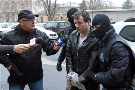 """Lehel, alleged hacker """"Guccifer"""", is escorted by masked policemen in Bucharest, after being arrested in Arad"""