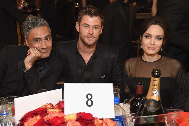 Chris Hemsworth sitting next to director of Thor, Taika Waititi, and Angelina Jolie at the Golden Globes