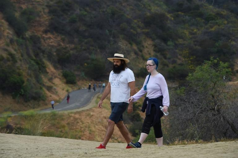 Chuck McCarthy chats with his client Anie Dee (R) as they walk in the Hollywood Hills in Runyon Canyon Park