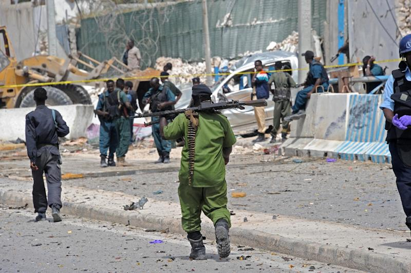 Somali soldiers secure a damaged perimeter wall following twin car bombings near Mogadishu's airport which left 13 dead