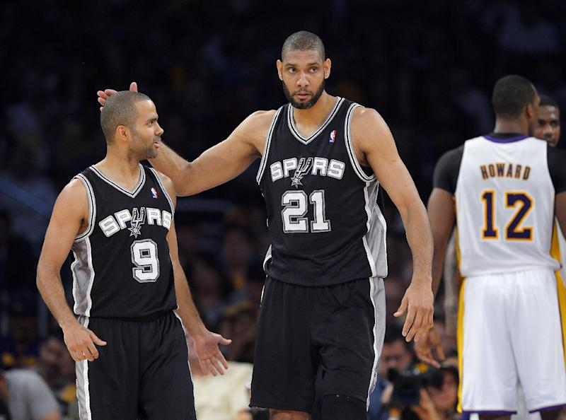 San Antonio Spurs forward Tim Duncan (21) pats guard Tony Parker (9), of France, on the head after he scored as Los Angeles Lakers center Dwight Howard (12) faces away during the first half in Game 4 of a first-round NBA basketball playoff series, Sunday, April 28, 2013, in Los Angeles. (AP Photo/Mark J. Terrill)