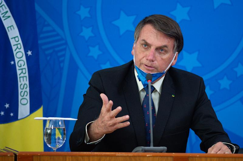 BRASILIA, BRAZIL - MARCH 20: Jair Bolsonaro President of Brazil takes off his protective mask to speak to journalists during a press conference about outbreak of the coronavirus (COVID - 19) at the Planalto Palace on March 20, 2020 in Brasilia, Brazil. (Photo by Andressa Anholete/Getty Images)