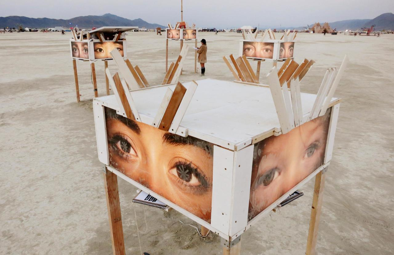 A participant looks at art works on the playa at sunrise, during the 2013 Burning Man arts and music festival in the Black Rock desert of Nevada, August 29, 2013. The federal government issued a permit for 68,000 people from all over the world to gather at the sold out festival, which is celebrating its 27th year, to spend a week in the remote desert cut off from much of the outside world to experience art, music and the unique community that develops. REUTERS/Jim Bourg (UNITED STATES - Tags: SOCIETY) FOR USE WITH BURNING MAN RELATED REPORTING ONLY. FOR EDITORIAL USE ONLY. NOT FOR SALE FOR MARKETING OR ADVERTISING CAMPAIGNS. NO THIRD PARTY SALES. NOT FOR USE BY REUTERS THIRD PARTY DISTRIBUTORS