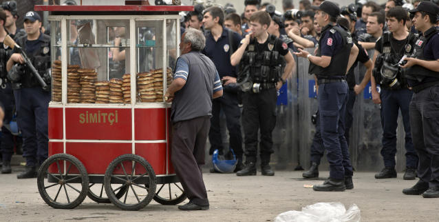 A pretzels vendor maneuvers his cart in front of a large group of riot police in Taksim square in Istanbul, Turkey, Wednesday, June 12, 2013. Riot police fired tear gas, water cannon and rubber bullets in day-long clashes that lasted into the early hours Wednesday, battling protesters who have been occupying Istanbul's central Taksim Square and its adjacent Gezi Park in the country's most severe anti-government protests in decades.(AP Photo/Vadim Ghirda)