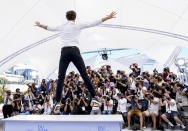 FILE - In this July 17, 2021 file photo Pierre Niney jumps from the plinth at the photo call for the film 'OSS 117: From Africa with Love' at the 74th international film festival, Cannes, southern France. (AP Photo/Brynn Anderson, File)