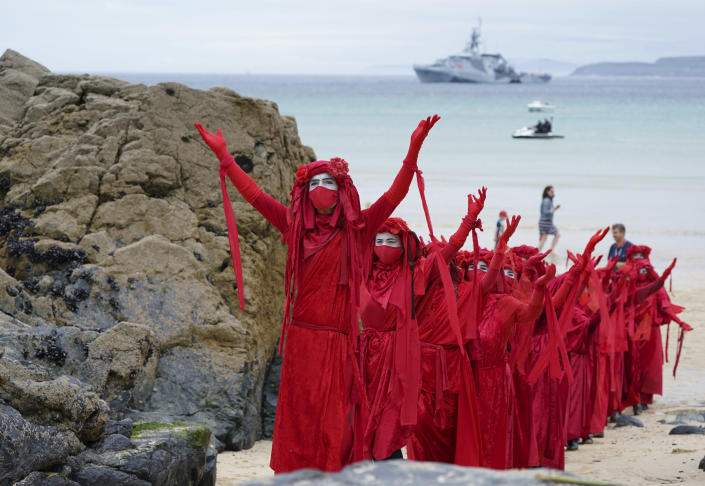 Protestors in costumes march on the beach of Carbis Bay outside the G7 meeting taking place in St. Ives, Cornwall, England, Friday, June 11, 2021. Leaders of the G7 begin their first of three days of meetings on Friday in Carbis Bay, in which they will discuss COVID-19, climate, foreign policy and the economy. (AP Photo/Jon Super)