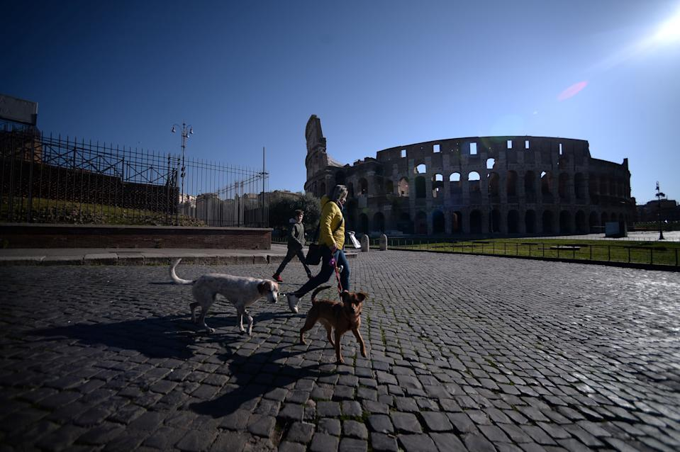 A woman walks her dogs across the deserted surroundings of the closed Colosseum monument on March 16, 2020 in Rome. (Photo by Filippo MONTEFORTE / AFP) (Photo by FILIPPO MONTEFORTE/AFP via Getty Images)