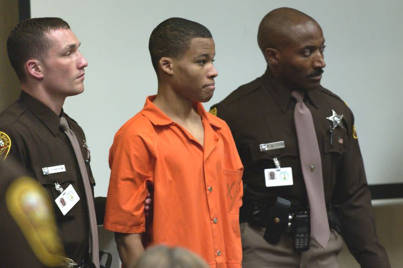 FILE PHOTO: FILE PHOTO : 18-year old sniper suspect Malvo is surrounded by deputies as he is brought into court to be identified by a witness during the trial of sniper suspect John Allen Muhammad at the Virginia Beach Circuit Court in Virginia Beach